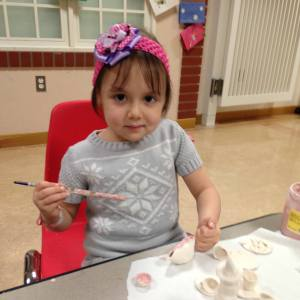 A childhood cancer patient participating in a Tracy's Kids program receiving a bow headband this past holiday season, provided through a special CCCA donation match initiative.